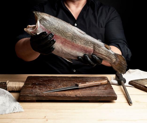 Шеф-повар в черной рубашке и черных латексных перчатках держит сырой тушу лосося без головы