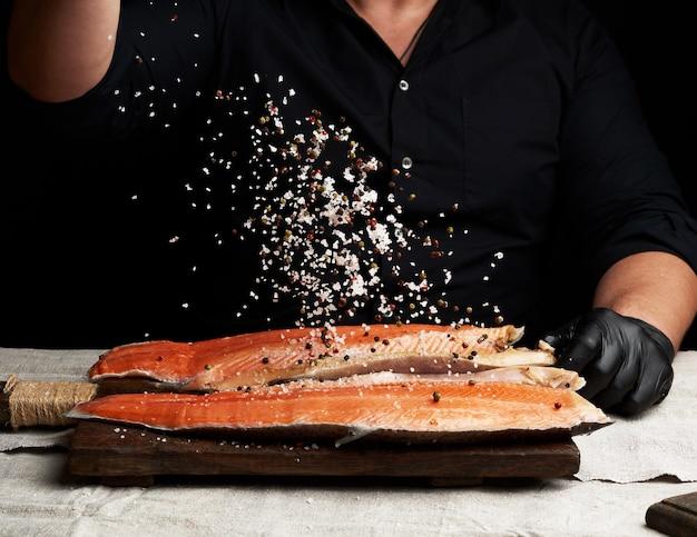 黒のシャツと黒のラテックス手袋のシェフが木製のまな板にサーモンの切り身を準備します