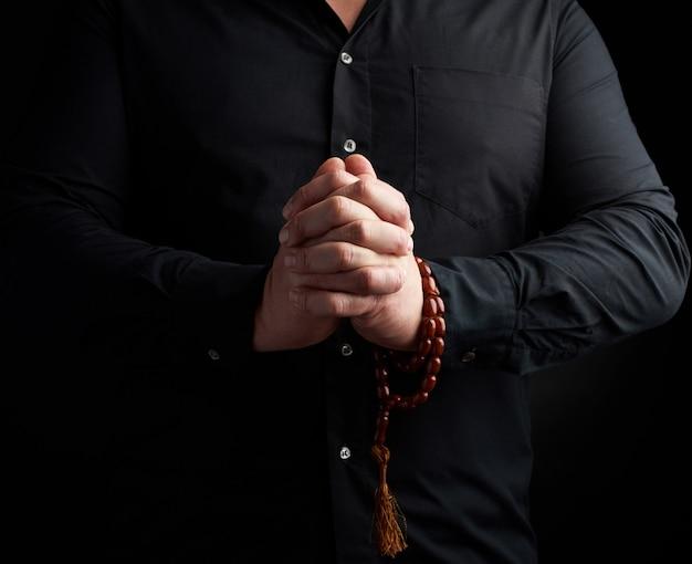 黒いシャツを着た男が彼の胸の前で手をつないだ