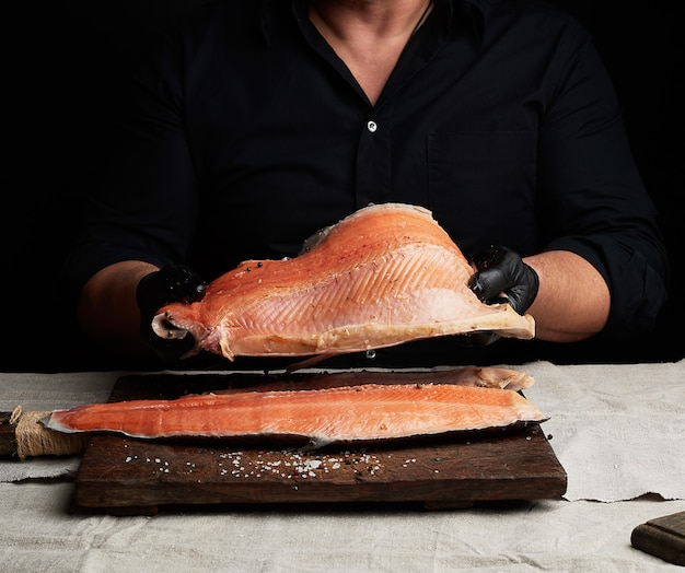 Шеф-повар в черной рубашке и черных латексных перчатках держит над столом большой кусок филе лосося