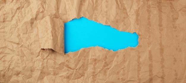 Текстура мятой бумаги из коричневого листа бумаги с жирными пятнами и большим отверстием с закрученным углом