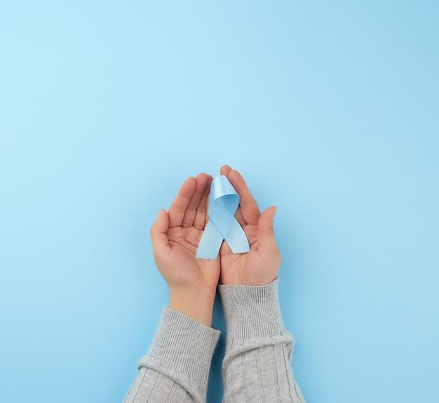 人は手のひらにループに折り畳まれた青い絹のリボンを保持します
