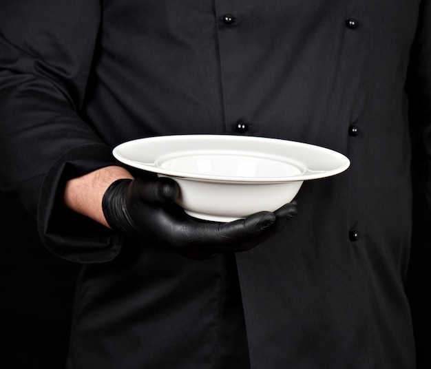 黒い制服と黒いラテックス手袋で調理することは彼の手に丸い空の白いプレートを保持します