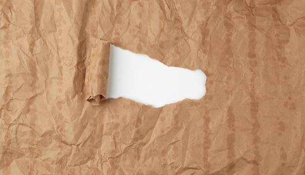 Текстура мятой бумаги из коричневого листа бумаги с жирными пятнами и большим отверстием
