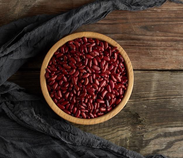 Сырые круглые красные бобы в тарелке на деревянном столе