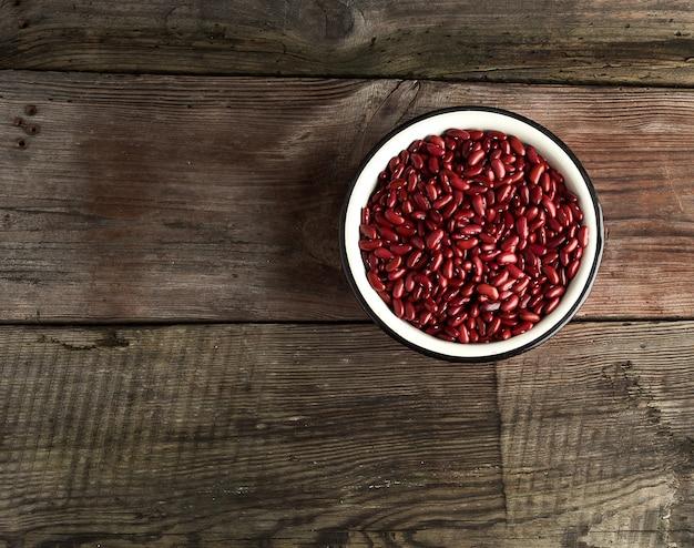 Сырье овальной красной фасоли в тарелку на деревянном столе