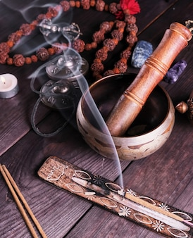 銅の歌ボウルと茶色のテーブルの上の木の棒