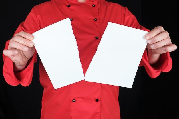 赤い制服を着た男は半分に引き裂かれた紙の白いシートを保持します。