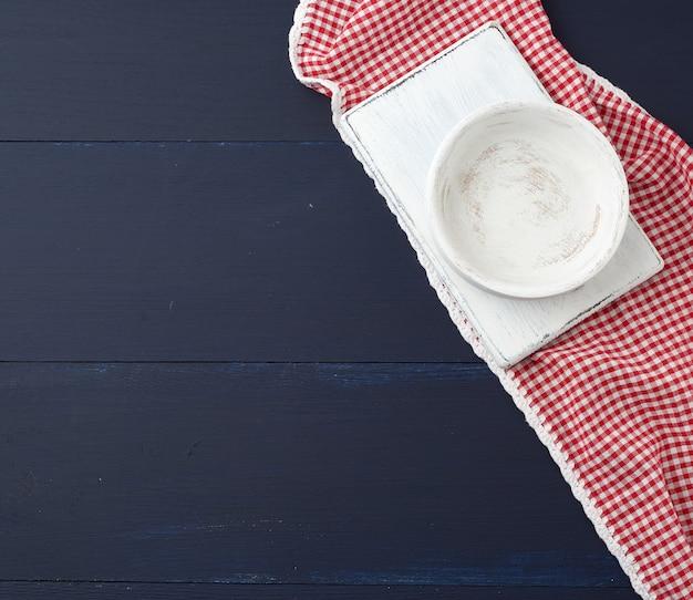長方形の白い切断キッチンボードと青い木製の表面に空の丸皿