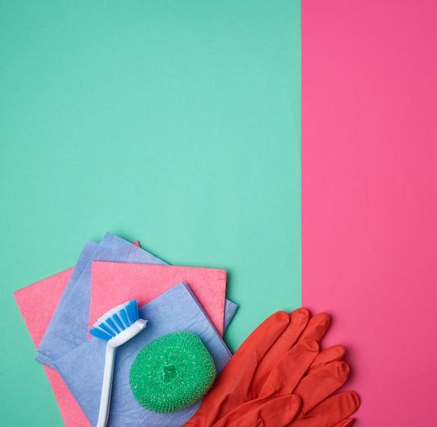 Предметы для домашней уборки с красными резиновыми перчатками, кисточкой, разноцветными губками для пыли