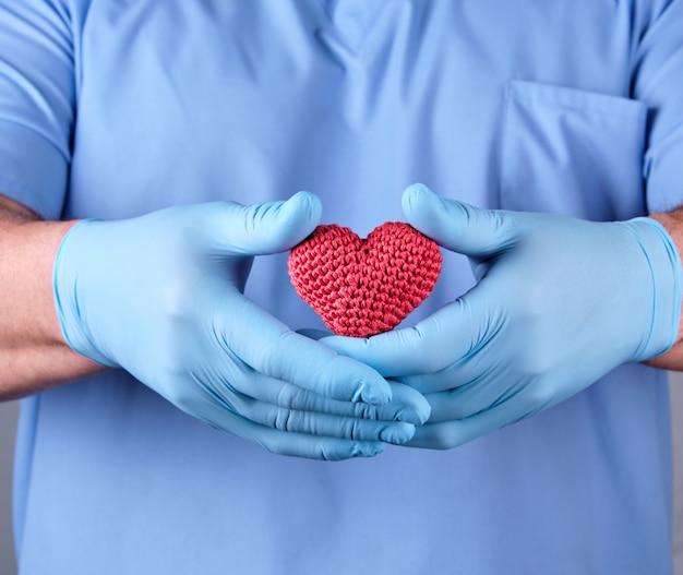 Доктор с синими латексными перчатками держит красное сердце