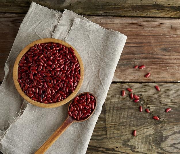 Сырцовые овальные красные фасоли в плите на деревянном столе. органическая еда
