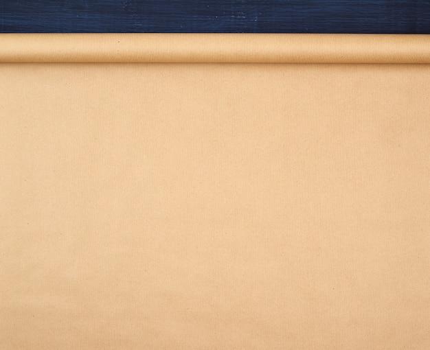 青い木製の背景に茶色のクラフトペーパーのねじれのないロール