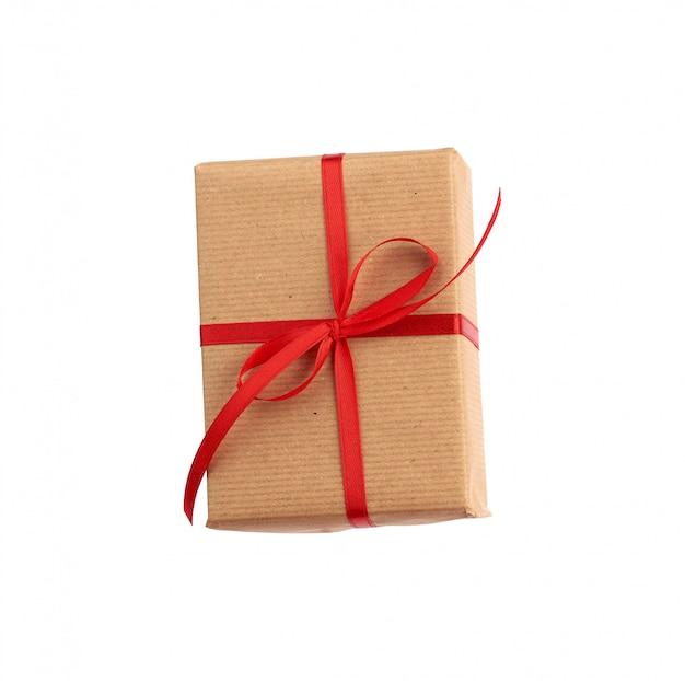 Прямоугольная коробка, завернутая в коричневую бумагу и перевязанная красным бантом
