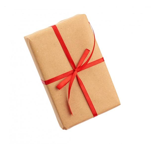 Прямоугольная коробка, завернутая в коричневую бумагу и перевязанная красным бантом, подарок на белом фоне
