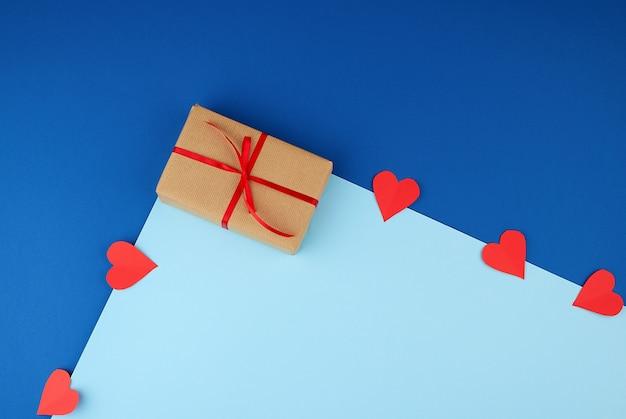 Завернутая квадратная коробка с подарком из коричневой крафт-бумаги и перевязанная тонкой шелковой красной лентой
