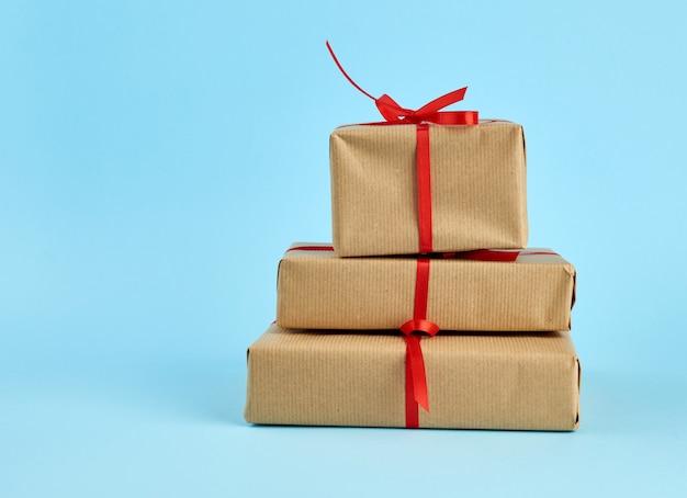 Стопка коробок, завернутых в коричневую бумагу и перевязанных красным бантом