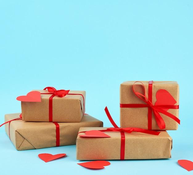 Стек обернутых подарков в коричневой крафт-бумаге и перевязанный красной лентой