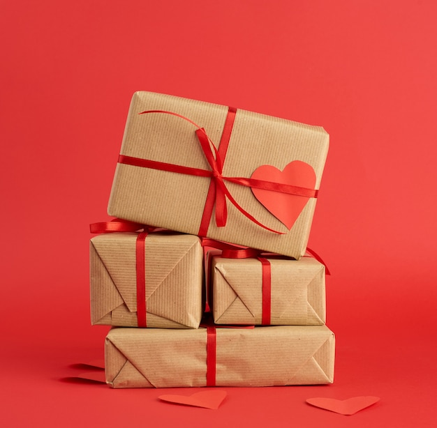 Стек обернутых подарков в коричневой крафт-бумаги и перевязанный красной лентой на красном
