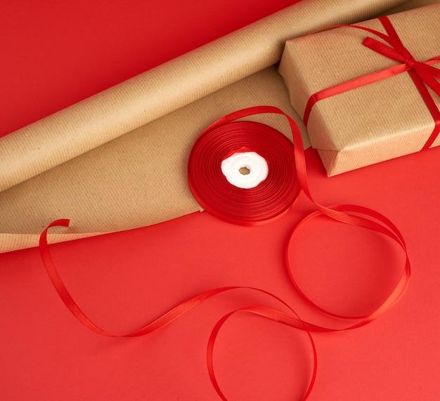 Бумага для упаковки, бобина с красной лентой и упакованный подарок в коричневой крафт-бумаге