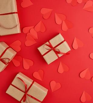 Коробки, завернутые в коричневую крафт-бумагу и перевязанные красной тонкой шелковой лентой на красном