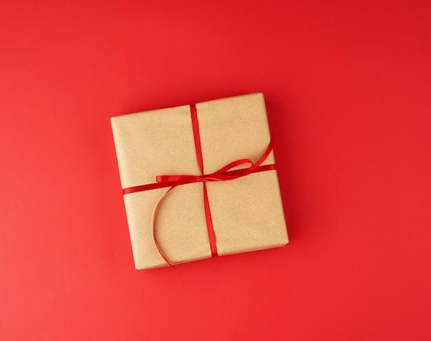 Квадратная коробка, завернутая в коричневую крафт-бумагу и обвязанная красной тонкой шелковой лентой