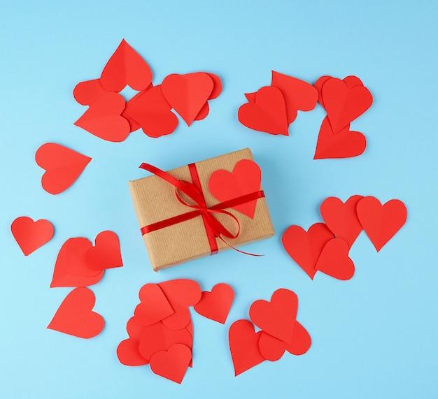 Прямоугольная коробка обернута в коричневую бумагу и обвязана красной тонкой шелковой лентой