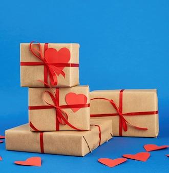 Стопка обернутых подарков в коричневую крафт-бумагу и перевязанную красной лентой на синем