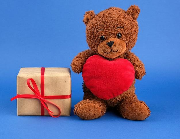 Квадратная коробка, обернутая коричневой крафт-бумагой и обвязанная красной тонкой шелковой лентой рядом с коричневым плюшевым мишкой