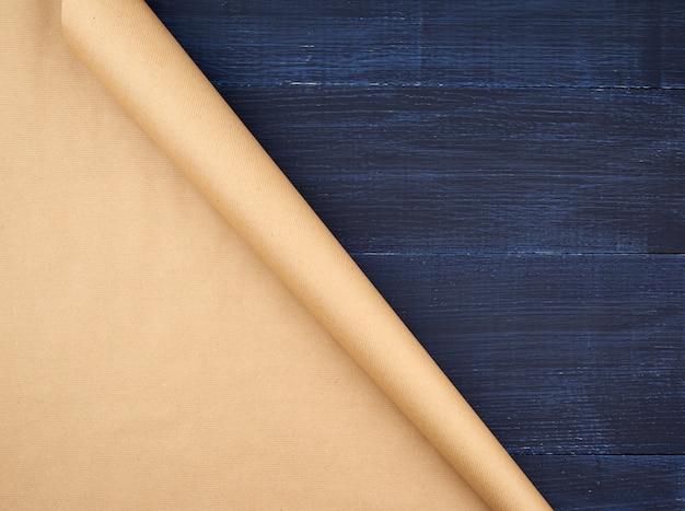 青い木製の背景、空スペースに茶色のクラフトペーパーのねじれのないロール。古いクラフト紙のテクスチャ