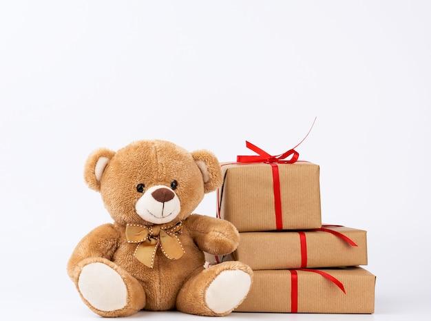 Милый плюшевый мишка бежевый и стопка подарков в коробках, завернутых в коричневую эко-бумагу
