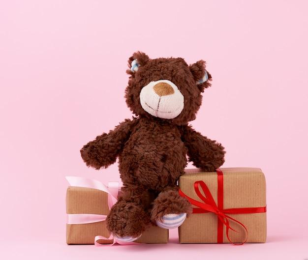Коричневый милый плюшевый мишка и подарки, завернутые в коричневую эко крафт-бумагу и перевязанные лентой