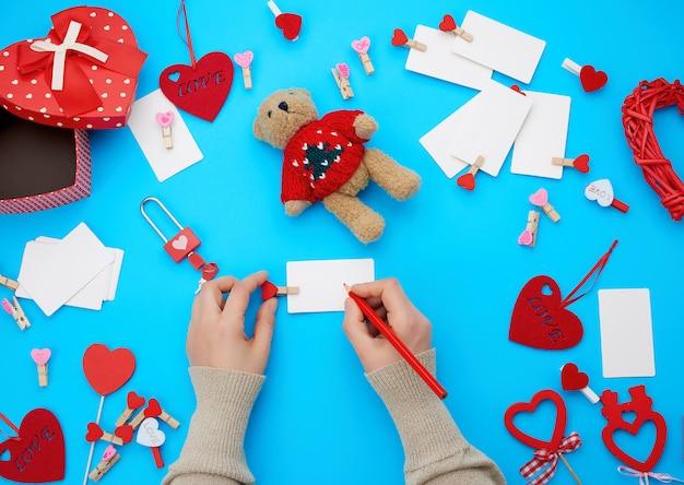 女性の手は赤い木製の鉛筆を保持し、段ボール箱の横にある白い紙の名刺に書き込みます