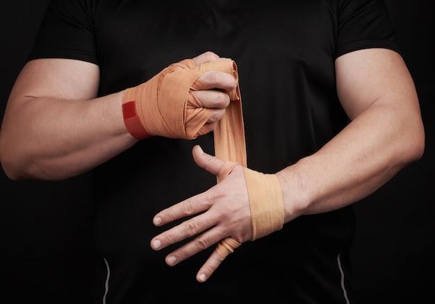 Спортсмен встает в черную одежду и оборачивает руки в красный текстильный эластичный бинт
