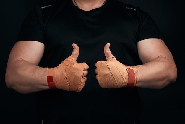 Мускулистый атлет в черной униформе показывает как символ двумя руками