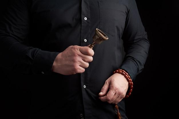 黒いシャツを着た成人男性は銅のチベットの儀式の鐘を保持しています