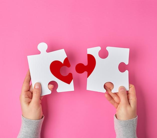 Женские руки держат большие белые пазлы с кусочком красного сердца