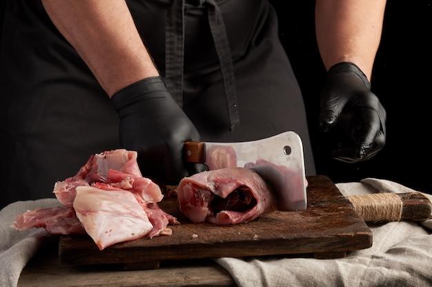 Шеф-повар в черных латексных перчатках держит большой нож и разрезает на куски сырое мясо кролика
