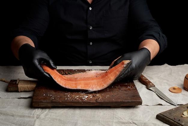 Шеф-повар в черной рубашке и черных латексных перчатках держит большой кусок филе лосося