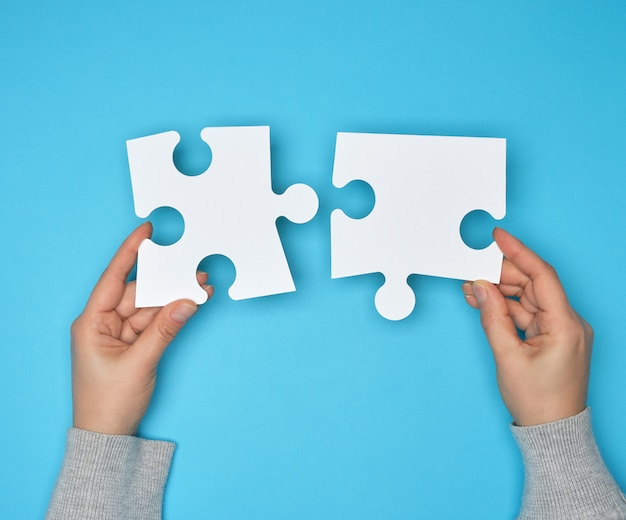 Две женские руки держат большие бумажные белые пустые пазлы