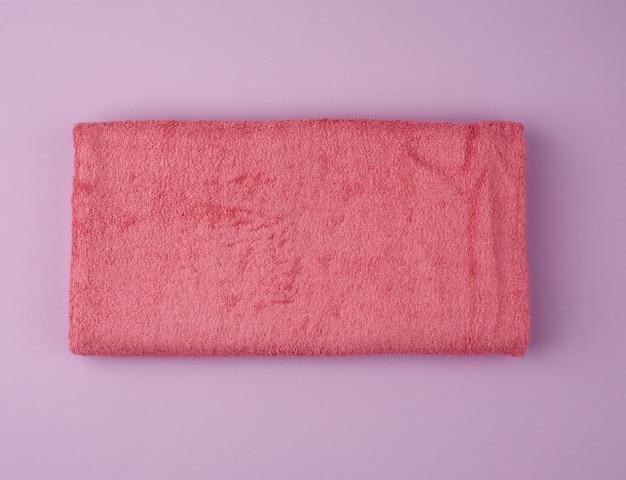 Сложенная банная махровая розовая салфетка на белом фоне