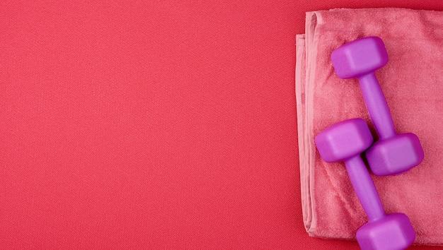 赤いネオプレンマットに紫色のプラスチックダンベルとピンクのテリー織りのタオルのペア