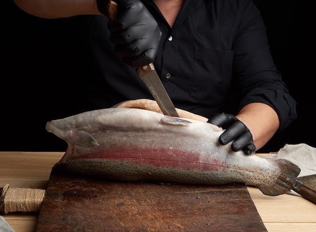Шеф-повар в черной рубашке и черных латексных перчатках нарезает целую свежую рыбу лососем