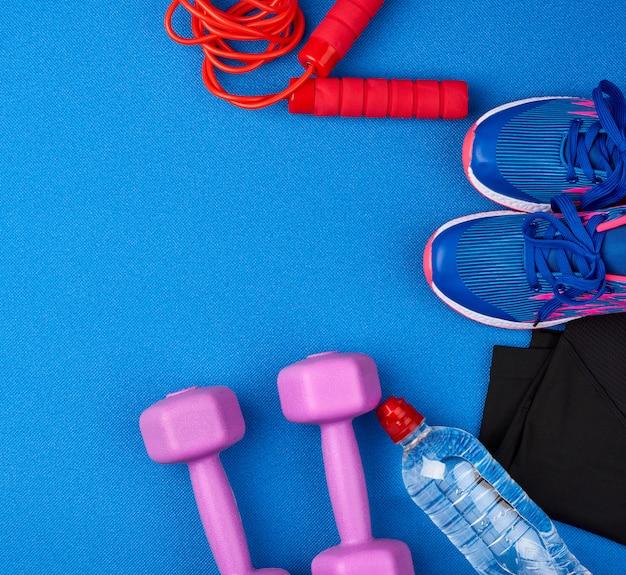 プラスチック製の紫色のダンベル、スポーツウェア、水、青色の背景にピンクのスニーカー