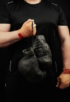 Мускулистый спортсмен в черной униформе держит в руке очень старые черные боксерские перчатки