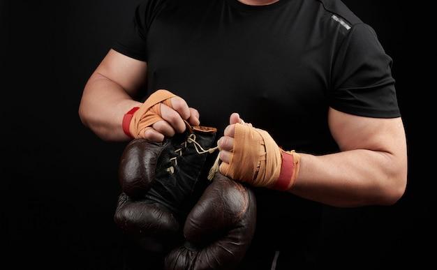 Мускулистый спортсмен в черной униформе держит в руке очень старые коричневые боксерские перчатки, его руки перевязаны