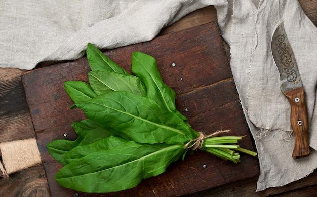 新鮮なスイバの葉と古い茶色のまな板の束