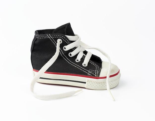 紐のない白い靴ひもが付いた黒いテキスタイルの子供用スニーカー