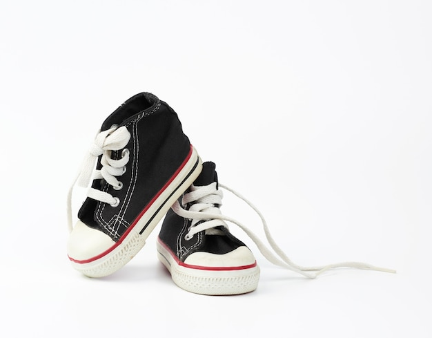 黒いテキスタイルの子供用スニーカーと白い紐のない靴ひも