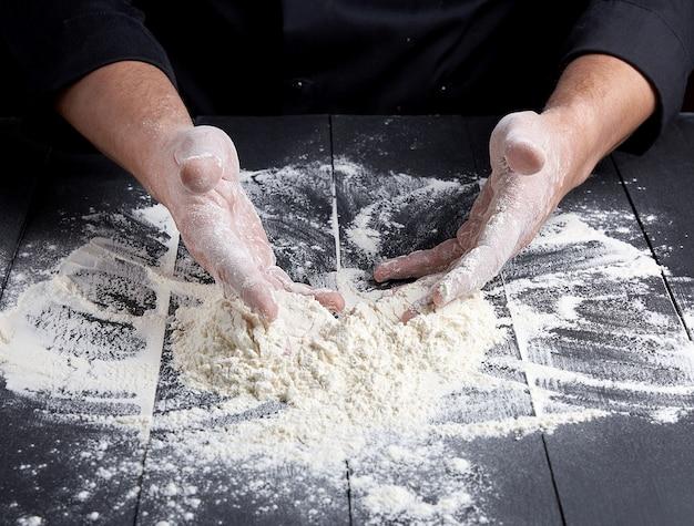 木製の木製テーブルの上に散らばって白い小麦粉